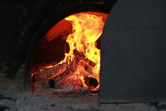 Bright fire burning in the oven covered with a door rail.  Stock Images