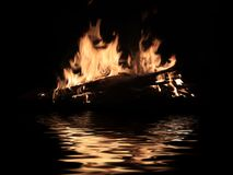 Bright fire of burning shipwreck debris. On the surface of the water royalty free stock image