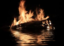 Bright fire of burning shipwreck debris. On the surface of the water stock photos