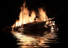 Burning shipwreck debris. Bright fire of burning shipwreck debris on the surface of the water royalty free stock images