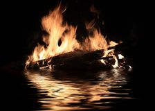 Bright fire of burning shipwreck debris. On the surface of the water royalty free stock photography