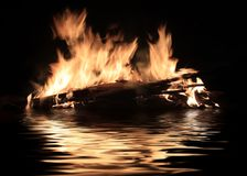 Burning shipwreck debris. Bright fire of burning shipwreck debris on the surface of the water stock photos