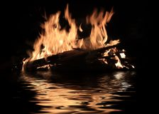 Burning shipwreck debris. Bright fire of burning shipwreck debris on the surface of the water royalty free stock photos