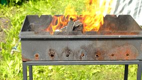 Bright flame when burning wood in a metal fireplace outdoors, hot fire and coals for barbecue, nature yellow fire in the