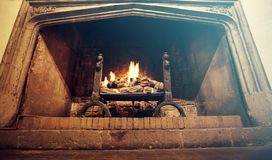 Antique fireplace. Bright flame of fire burns in an old fireplace of a castle in England stock photo