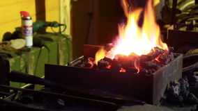 Bright flame over coals in a forge stock video footage