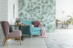 Monstera wallpaper in living room. Bright flat with white brick wall and monstera leaves wallpaper in botanic living room Royalty Free Stock Photography