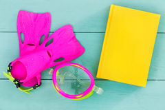 Bright flippers, goggles and book on a green table Stock Photo