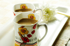 Bright floral tea cups. Milk tea in floral tea cups royalty free stock photos