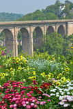 Bright Flowerbed and tall stone bridge Royalty Free Stock Photos