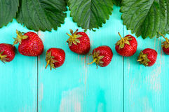 Bright food background. Fresh strawberries and green leaves on a wooden board. Stock Image