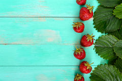 Bright food background. Fresh strawberries and green leaves on a wooden board. Royalty Free Stock Photos