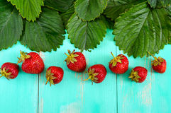 Bright food background. Fresh strawberries and green leaves on a wooden board. Stock Images