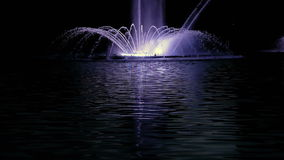 Bright fountain on the water pond or river. Fountain with bright illumination on the water pond or river with beautiful reflection at the evening or night stock video footage