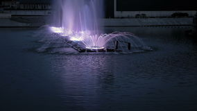 Bright fountain on the water pond or river. Fountain with bright illumination on the water pond or river with beautiful reflection at the evening or night stock video