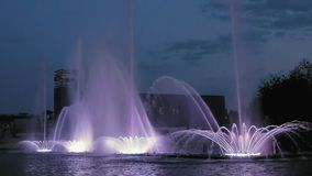 Bright fountain on the water pond or river. Fountain with bright illumination on the water pond or river with beautiful reflection at the evening or night stock footage