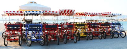 Bright four-wheeled bicycles with striped cloth roofs. Sea beach in Greece with tourist four-wheeled cycles with red and blue striped roofs Royalty Free Stock Photos