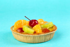 Bright fresh cake with fruit. On a blue background Royalty Free Stock Photo