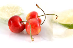 Bright fresh cherries - closeup. Three bright colorful cherries with frosen limes and ice-cubes - closeup Royalty Free Stock Photo