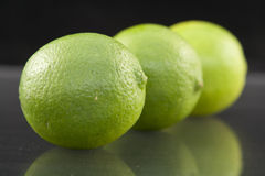 Bright fresh green limes on dark background Royalty Free Stock Photos