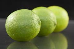 Bright fresh green limes on dark background Royalty Free Stock Photos