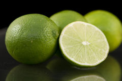 Bright fresh green limes on dark background royalty free stock photo