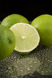 Bright fresh green limes on dark background Stock Image