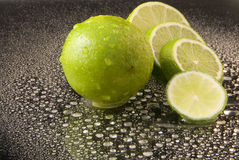 Bright fresh green limes on dark background Stock Images