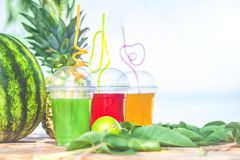 Bright Fresh healthy juices, fruit, pineapple, watermelon on the background of the sea. Summer, rest, healthy lifestyle. Copy space royalty free stock images
