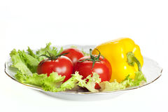 Bright fresh vegetables. Salad, tomato and pepper on a plate image isolated on a white background Royalty Free Stock Images