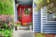 Bright front red door to blue American home with floral exterior Royalty Free Stock Image