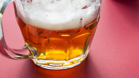 Bright frothy beer on a glass jar and red background Royalty Free Stock Photo
