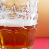 Bright frothy beer on a glass jar and red background Stock Photos