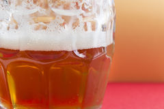 Bright frothy beer on a glass jar and red background Royalty Free Stock Photography