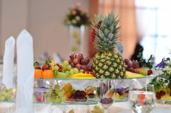 Bright fruit on the festive table. Dish with bright fruit pineapple, grapes, strawberries, currants, kiwi fruit on the festive table Royalty Free Stock Photography