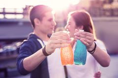 Lovely hugging couple being close to each other while clinking bottles stock images