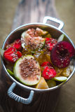 Bright fruit salad with figs and strawberries in a tin bowl on a wooden stand Stock Images