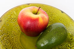 Bright fruits. Fruits of Apple and avocado on green plate Stock Photo