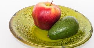Bright fruits. Fruit avocado, Apple green plate Royalty Free Stock Photos