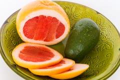 Bright fruits. Fruit grapefruit, avocado green plate Royalty Free Stock Photo