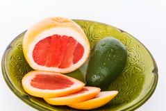 Bright fruits. Fruit grapefruit, avocado green plate Stock Images