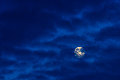 Bright full moon in blue sky with clouds Stock Photography