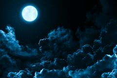 Bright full moon in the mystical midnight sky with stars surrounded by dramatic clouds. Dark natural background moon and clouds. Bright full moon in the mystical royalty free stock photo