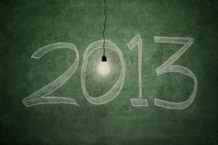Bright future at 2013. 2013 new year concept: an electric light bulb glowing bright in front of blackboard symbolising good year royalty free illustration