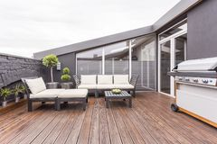 Cozy terrace with wooden floor. Bright garden furniture, grill and plants on cozy terrace with wooden floor and brick wall Royalty Free Stock Photography