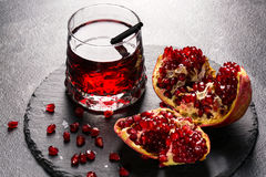 Bright garnet drink and a red pomegranate on a light gray background. Exotic ingredients for summer cocktails. Healthy Royalty Free Stock Photo