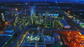 Bright gas and oil refinery plant at night aerial view. Brightly illuminated large gas and oil refinery plant with production towers and chimneys at summer night stock video