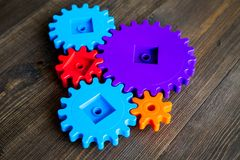 Bright gears for great technology of team work and correct mechanism on wooden background Stock Photos