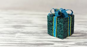 Bright gift box with a bow. Of blue and green colors with sparkles for the new year under the tree Stock Photography
