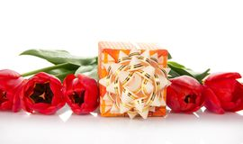 Bright gift box with a bow and the tulips Stock Photography